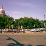 "Community Choice Act Now, Our Homes Not Nursing homes"" reads the giant banner held in front of the Texas Capitol, at 11th and Congress."