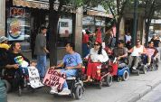 Jose Lara, Ruben Fernandez, Myra Murillo and other Desert ADAPTers in wheelchairs block the front of the inaccessible downtown burger king