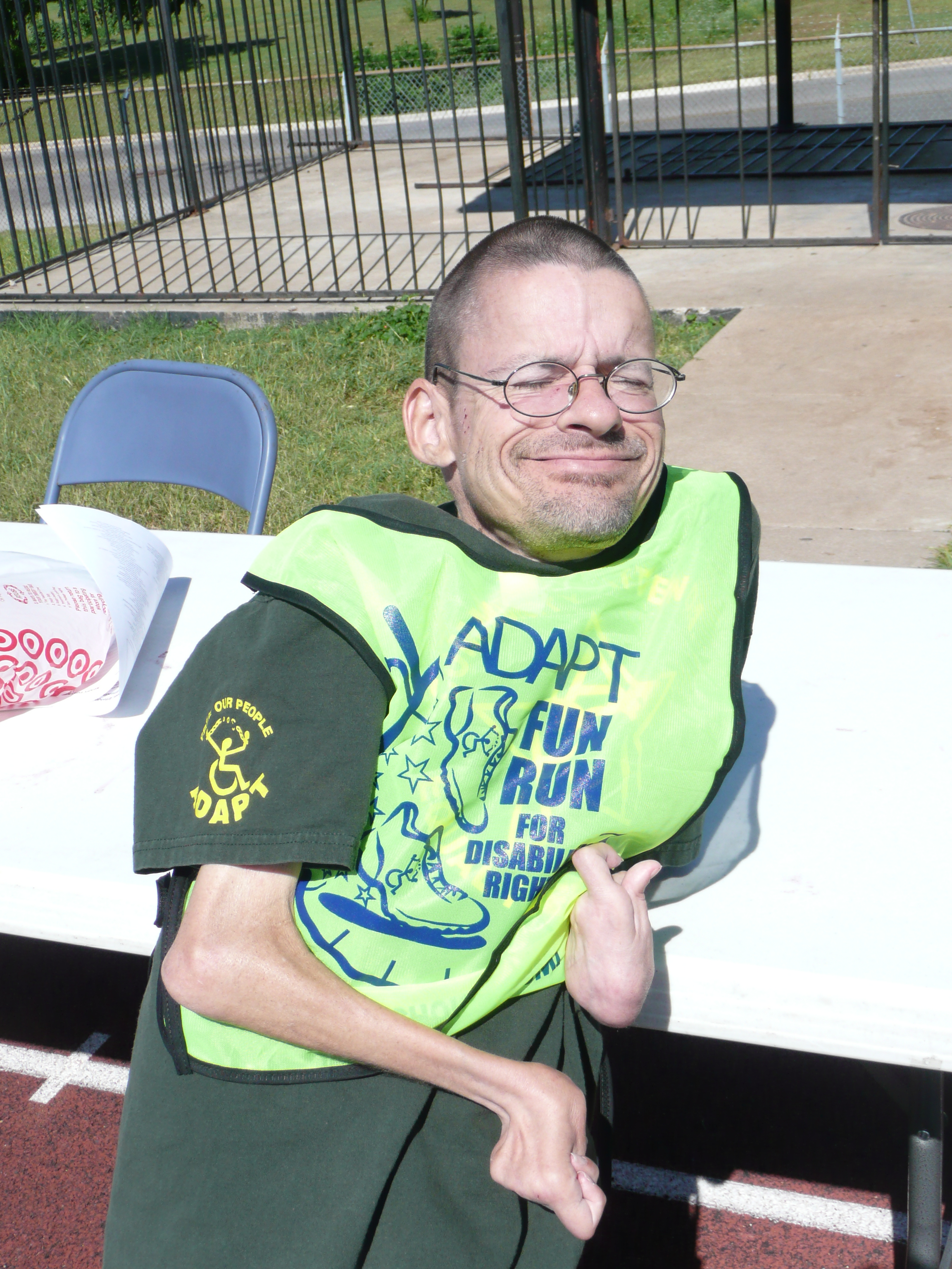 Bryson Smith leans back against a table. He is wearing his green FunRun vest and a big smile.