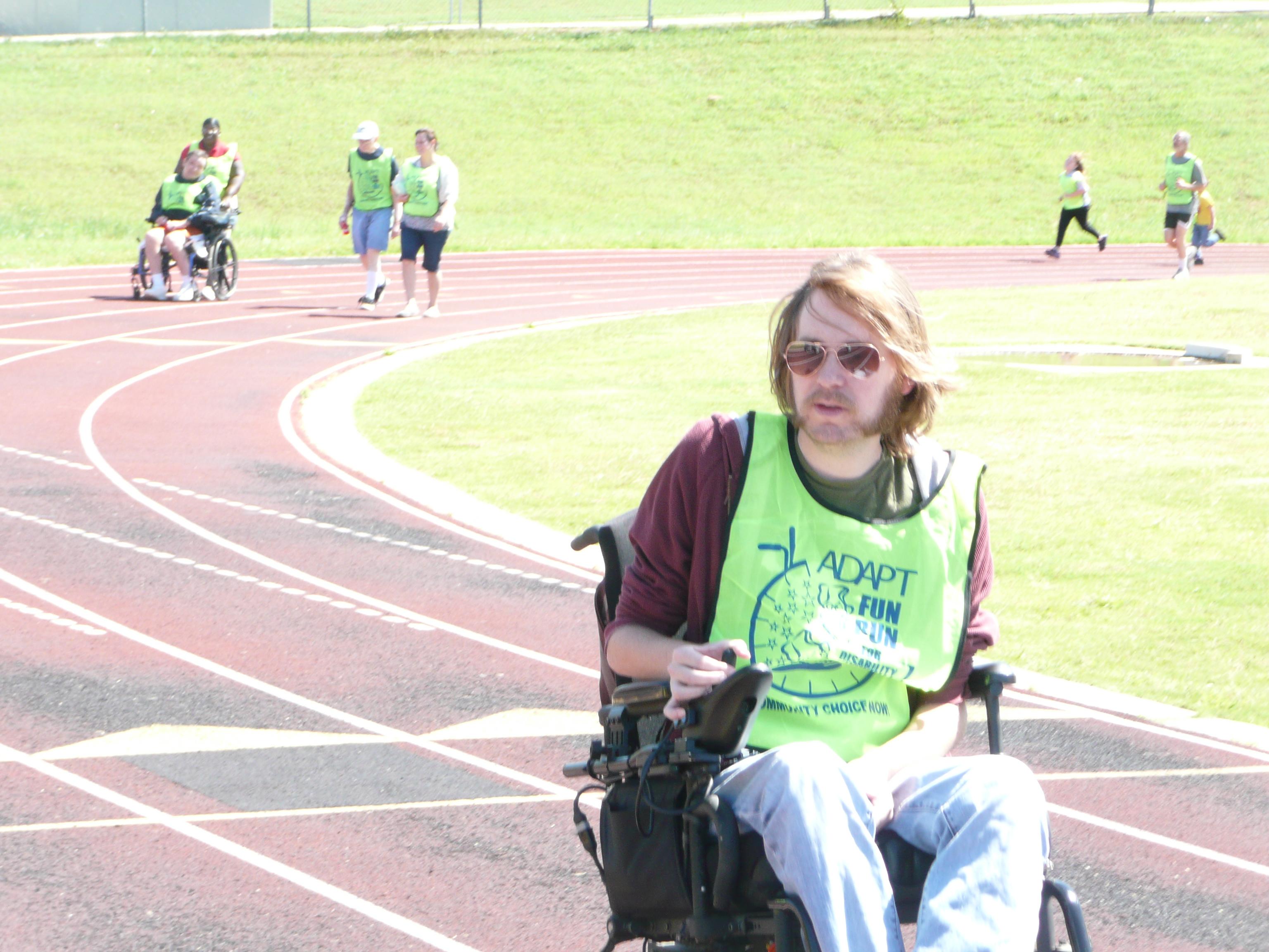 Eric Clow steers his motorized wheelchair around the Yellow Jacket Stadium track