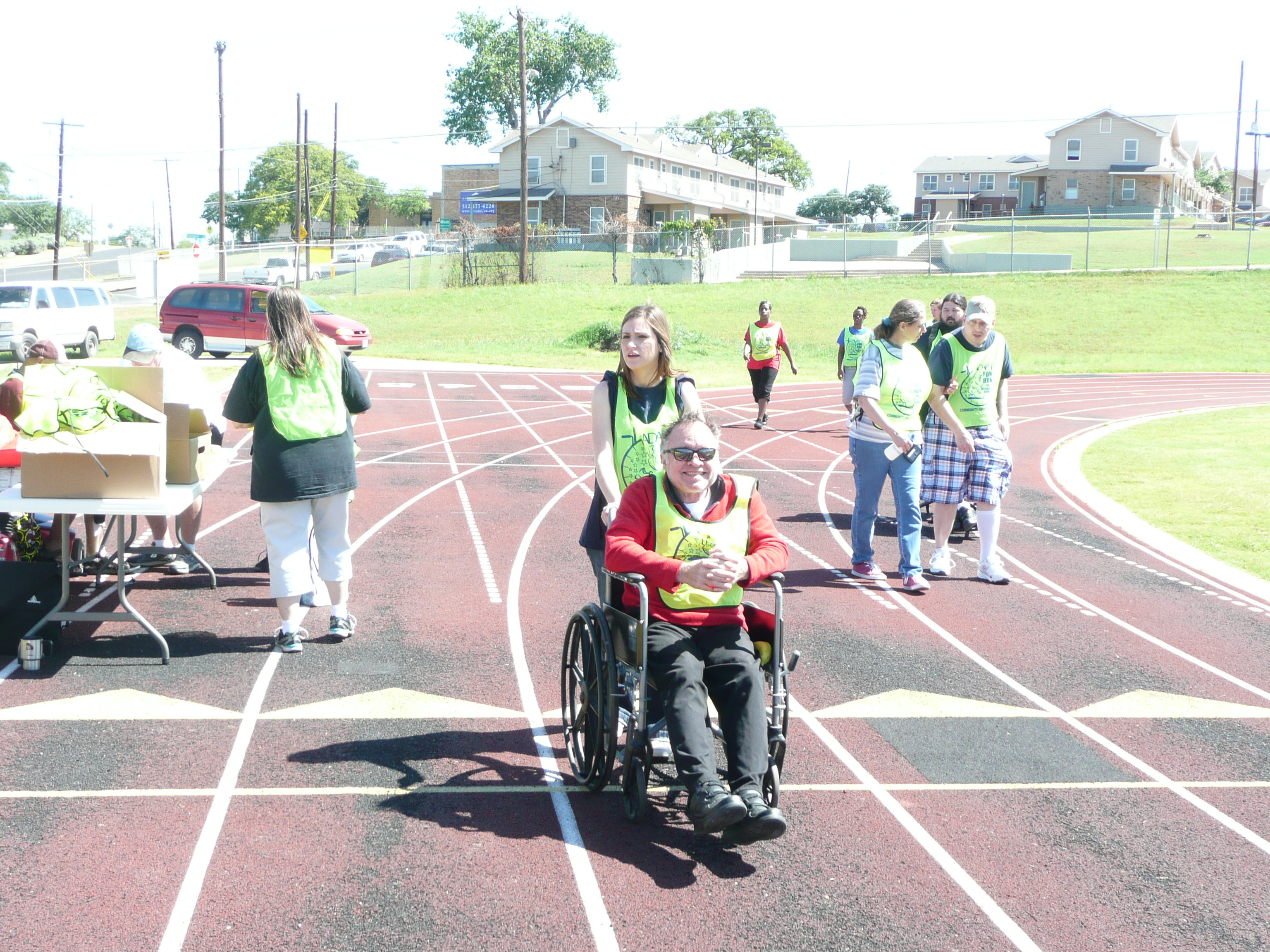 woman pushes man in a wheelchair while other people walk and run behind them on the track. On left side of picture woman walks up to a table.
