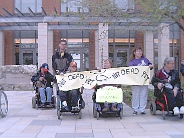 5 of the ADAPT protesters in wheelchairs and standing hold up Not Dead Yet banner