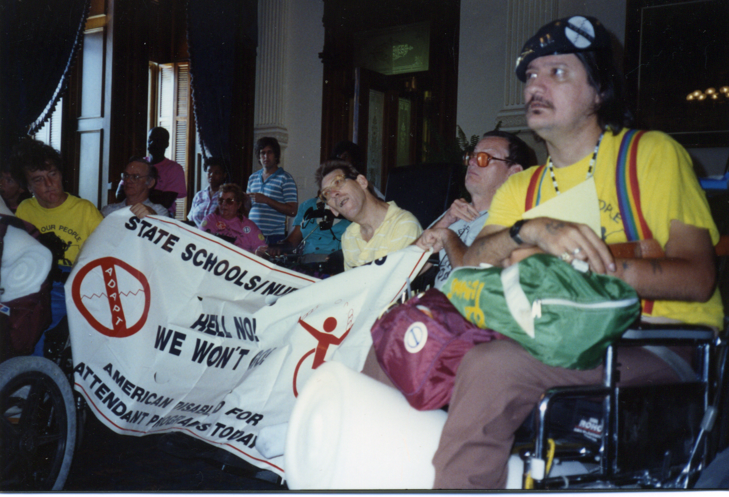 Lee Sanders, JT Templeton and Jim Wise hold up a huge banner from their wheelchairs in the hall in front of the Governor's office in the Texas Capitol.