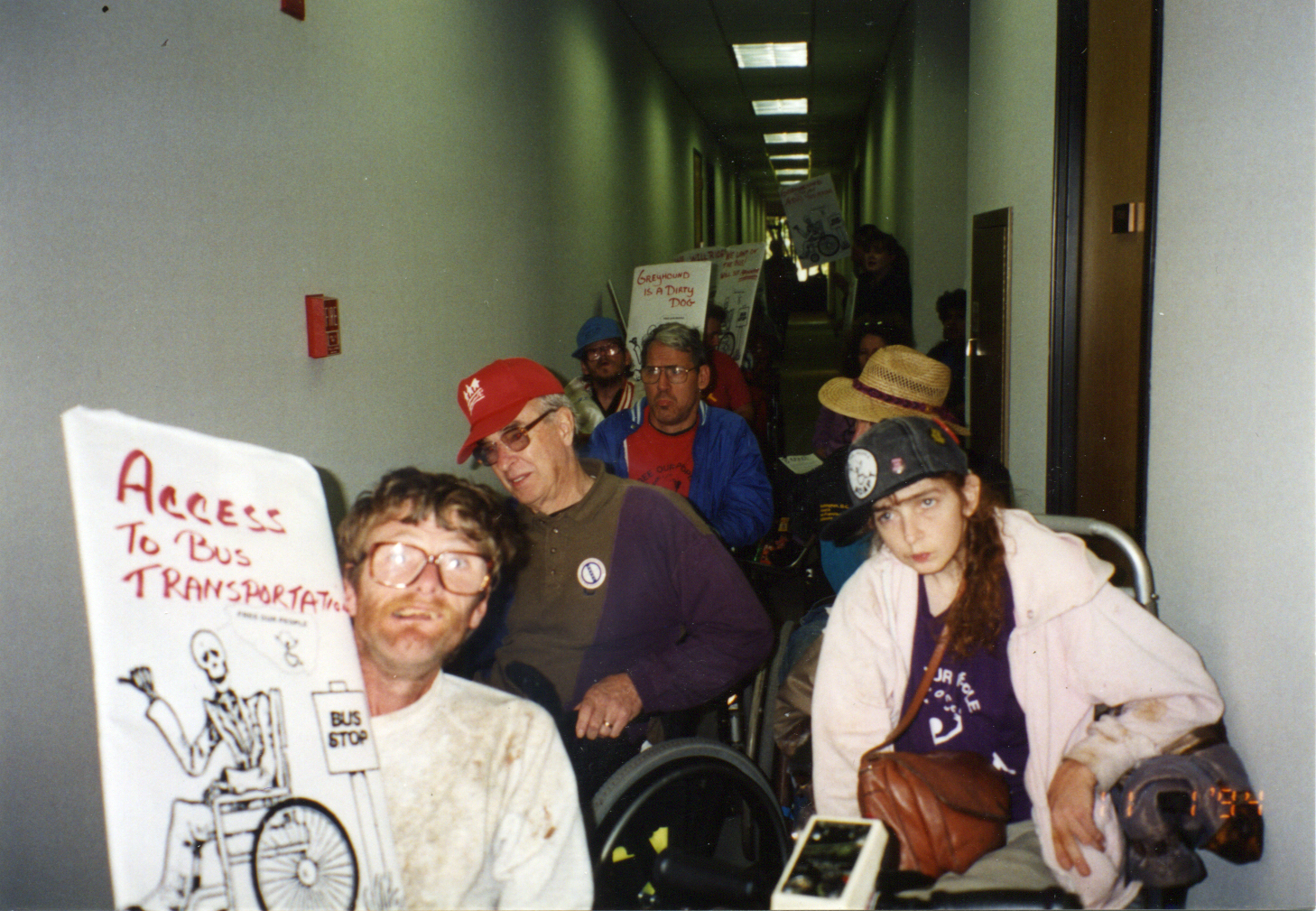 Sparky Metz, George Cooper and Rona Schnall along with other TX ADAPTers line the hallway demanding more community services. Sparky holds the Tired of Waiting skeleton in a wheelchair poster.