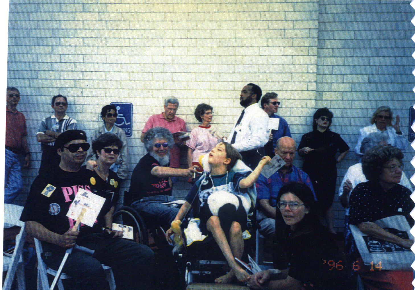 Bryce Thomas and Bob Kafka are surrounded by Texas ADAPTers protesting in front of white brick wall. Also visible are (L-R) Noel Velez, Carolyn Long, and Janet Thomas in foreground