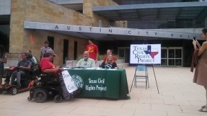 Members of ADAPT and TCRP at a table in front of the Austin City Hall