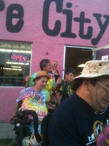 "Ron Cranston in his tie dye ADAPT shirt, Cathy Cranston and Dolores Carillo in PACT shirts, and Danny Saenz, as well as pink haired Treasure City saleswoman outside the front door. Pink wall behind reads ...""e City"""