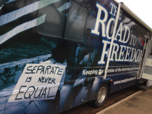 "The bus, with a picture of a woman marching with a sign saying ""Separate is never EQUAL"", hands handcuffed behind a wheelchair, and Road to Freedom"" written above Keeping the Promise of the ADA, www.roadtofreedom.net  and www.ada25.org"