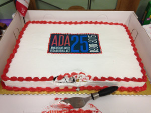 A cake with the ADA25 logo set in it's white frosting. A small piece is removed from the front as if someone could not quite wait.