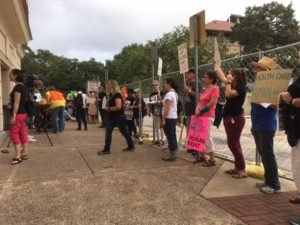Protesters stand in line along fence outside Hogg Auditorium calling for Cruz and Cornyn to oppose health care bill.