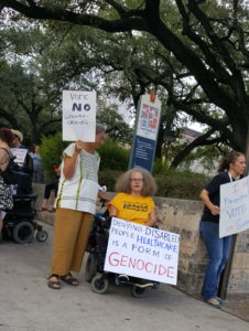 Flanked by two women, Stephanie Thomas in her wheelchair, holds a large sign that reads Denying Disabled People Health Care is Genocide.