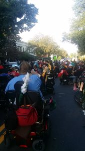 Large group of activists, many in wheelchairs gathered in front of a fancy house.  Shot from the back.