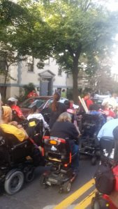 From the back, a group of people in wheelchairs are gathered in the street by parked cars,.  They appear to be heading toward a house.