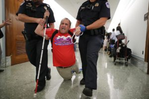 Blind man (Tom Earle) in a red ADAPT T-shirt and holding his white cane in one hand, is dragged down a hallway by two police officers.  An officer on each side holds his arms and his legs drag behind him.